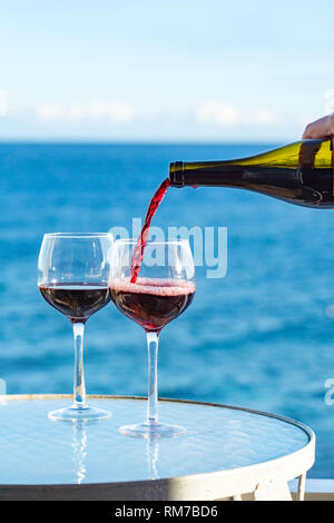 Waiter pouring aperitif red wine in glasses on outdoor tessace witn sea view in sunny day - Stock Image
