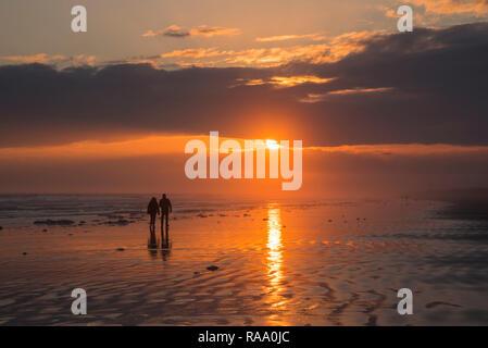 Couple walking into the sunset, Sunset Beach, North Carolina, United States - Stock Image