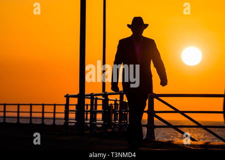 Aberystwyth, UK. 10th Apr, 2019. UK Weather: At the end of a day unbroken blue skies and warm spring sunshine, the sun sets  spectacularly behind the silhouettes of a man walking along the promenade  in Aberystwyth on the Cardigan Bay coast of West Wales. Credit: keith morris/Alamy Live News - Stock Image