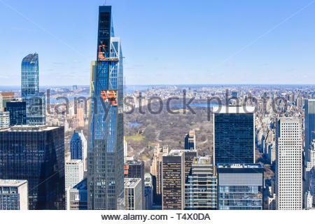 New York city, USA, urban skyline from a vantage point. A new skyscraper is under construction. Central Park has little color at the beginning of Spri - Stock Image