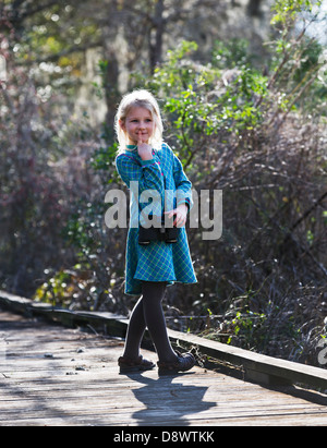 Girl standing on a boardwalk, with her finger to her lips-thinking.Wearing binoculards around her neck. - Stock Image