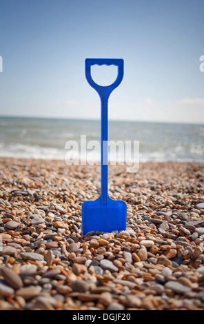 Blue spade stuck into pebbles on beach - Stock Image