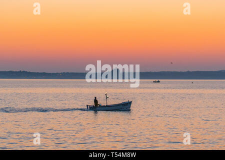 Newlyn, Cornwall, UK. 21st April 2019. UK Weather. These fishermen were out 3/4 of an hour before sunrise this morning, as the sky just started to take on an orange glow. Credit: Simon Maycock/Alamy Live News - Stock Image
