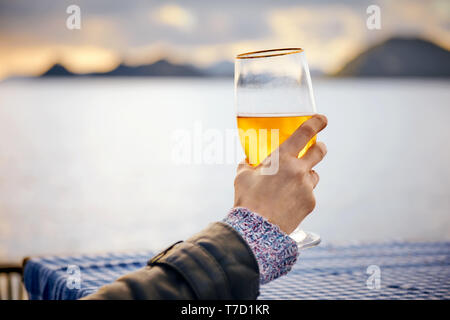 Close up hand of a woman holding a glass of beer with blurred sea, sky and island background at sunset. - Stock Image