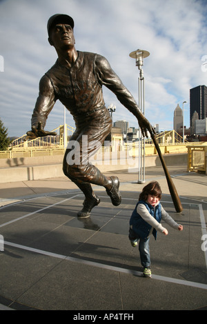 Boy in front of Roberto Clemente statue pretending to hit a home run, Pittsburgh, PA, USA - Stock Image