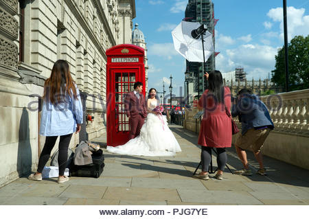Asian couple pose for wedding photos beside a traditional red telephone box, in Parliament Square, Westminster, London, UK. - Stock Image