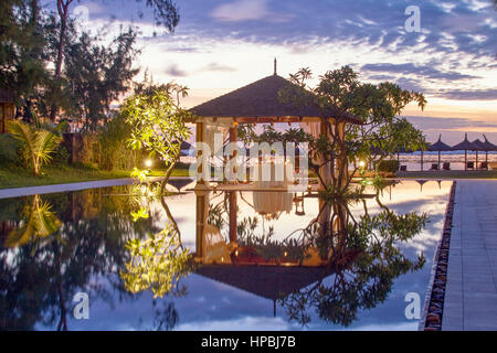 Resort Moevenpick at twilight, luxery table in small pavillion, sunset,  south coast of  Mauritius, Africa - Stock Image
