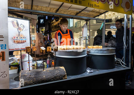 A street food stall holder in Myeongdong in Seoul, South Korea cooks Egg Buns. - Stock Image