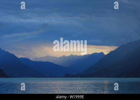 Summer scene at Lake Brienz. Last sunlight of the day and thunderstorm over Interlaken, Switzerland. - Stock Image