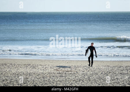 A surfer wearing a full body wet suit walks up the beach, away from the sea, carrying his surf board on a cold bright - Stock Image