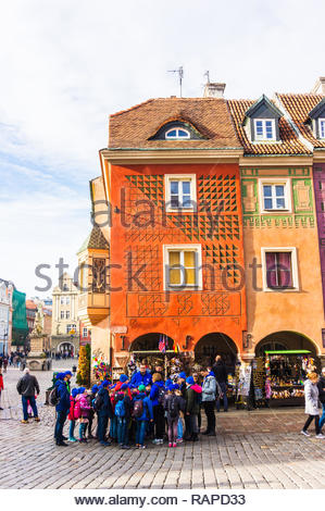 Poznan, Poland - November 12, 2018: Group of kids standing in front of a kiosk by colorful buildings on the old square. - Stock Image
