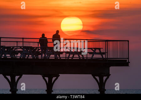 Aberystwyth Wales UK. 11 April 2019. UK Weather: The sun sets as a spectacular golden  globe behind  people silhouetted as they stand at the end of the pier in Aberystwyth on the Cardigan Bay coast of west Wales.