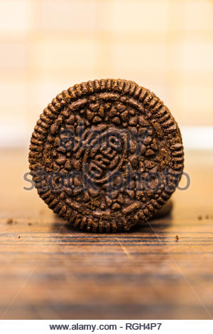 Poznan, Poland - January 25, 2019: Circle shaped crunchy brown Oreo biscuit on a wooden table in soft focus. - Stock Image