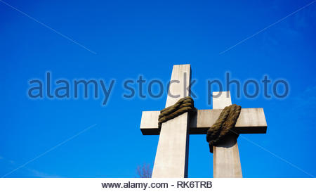 Poznan, Poland - February 6, 2019: Cross shaped sculpture of the 1956 uprising memorial and a blue sky. The historic landmark is located on the Adam M - Stock Image