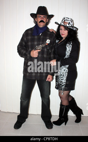 A MAN AND A WOMAN DRESSED IN COWBOY OUTFITS FOR A FANCY DRESS PARTY  VERTICAL PLAIN LIGHT BACKGROUND - Stock Image