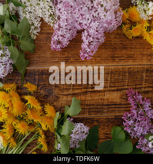 The decor of flowers on the background of vintage wooden planks. Vintage background with flowers of dandelion and lilac and a place under the text. Vi - Stock Image