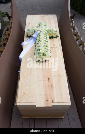 A cross made of flowers on a coffin on a charlot - Stock Image
