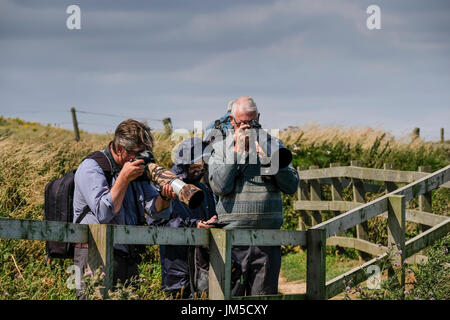 Two men with cameras using long lenses, bird watching bird watchers at a viewpoint on Bempton Cliffs RSPB Reserve, UK. A women is on her cellphone mob. - Stock Image