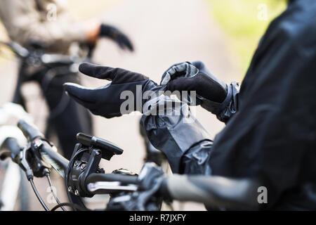 A close-up of a cyclist with electrobike putting on black gloves outdoors in park. - Stock Image