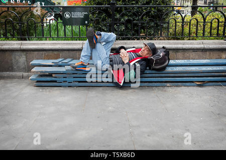 A man having a nap on some wooden planks outsdoors in Union Square Park in lower Manhattan, New York City. - Stock Image
