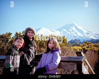 Mother, son, daughter, Taranaki volcano, Mount Egmont, New Zealand, sunny winter day. - Stock Image