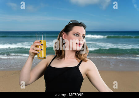 Drinking Orange Juice on the Beach. Attractive young women with a glass of orange juice posing on the beach. - Stock Image