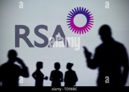 The Royal Sun Alliance (RSA) logo is seen on an LED screen in the background while a silhouetted person uses a smartphone (Editorial use only) - Stock Image