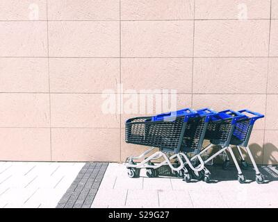 A line of shopping trolleys in front of a large wall outside a retail store in a minimalist environment - Stock Image