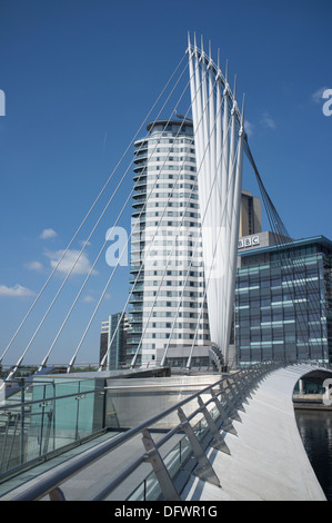 Footbridge at Salford Quays with BBC offices in the background set against a brilliant blue sky. - Stock Image