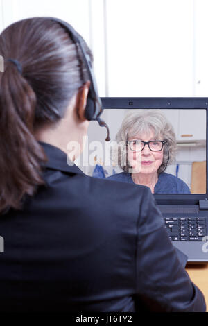 Rear view of a female lawyer or attorney in a black blazer with headset and laptop, having a online video chat with a senior woman, white copy space - Stock Image