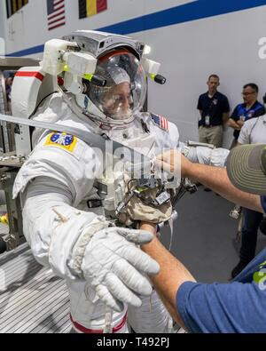 Boeing Commercial Crew Program astronaut Josh Cassada is assisted with his spacesuit before entering the pool at the Neutral Buoyancy Laboratory for ISS EVA training in preparation for future spacewalks while onboard the International Space Station at the Johnson Space Center April 12, 2019 in Houston, Texas. - Stock Image