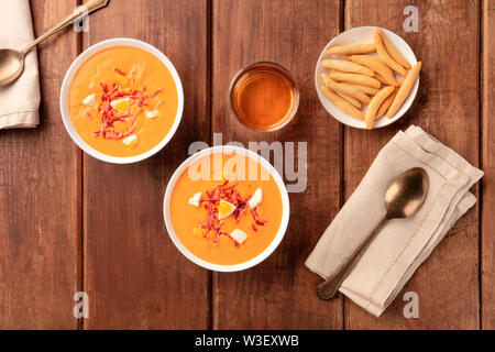 Salmorejo, Spanish cold tomato soup, shot from the top on a dark rustic wooden background with picos, typical breadsticks, and wine - Stock Image