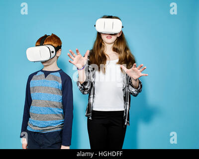 Boy and girl wearing virtual reality head gear, VR Glasses - Stock Image