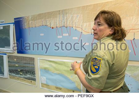 Information officer with California Department of Fish and Wildlife with map showing area of Refugio oil spill at JIC, Joint Information Center, for the Santa Barbara Refugio oil spill. - Stock Image