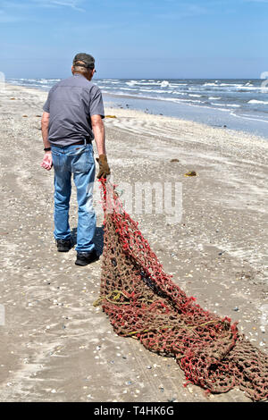 Volunteer removing hemp rope cargo net washed ashore with the incoming tide. - Stock Image