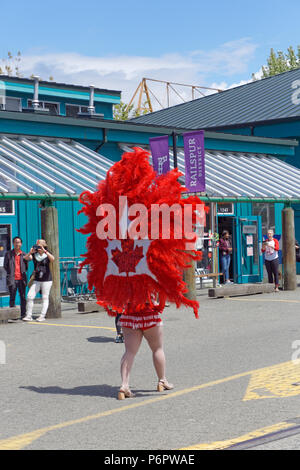 Vancouver, Canada.1st July, 2018. A Latin American dancer wearing a Canadian red maple leaf walks  in the annual Canada Day Parade on Granville Island, Vancouver, British Columbia. This year Canada Day celebrates the country's 151st birthday. Credit: John Mitchell/Alamy Live News - Stock Image