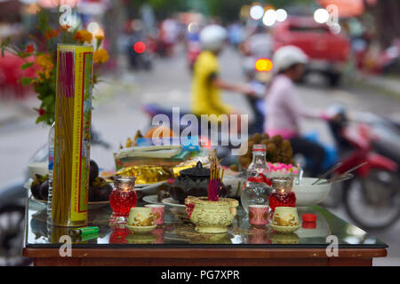 A small shrine set up with burning incense in the town of Hoi An, Central Vietnam. Shop owners periodically put up these shrines and burn fake money i - Stock Image