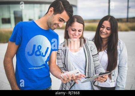 Drei Jugendliche mit Tablet und Smartphone unterwegs - Stock Image