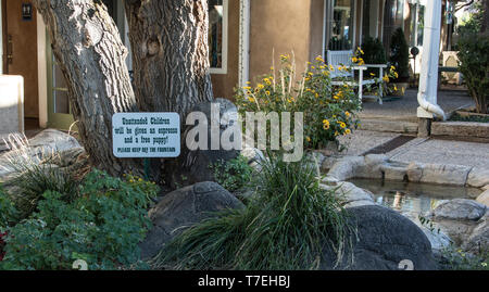 TAOS, NM, USA-9/27/15:  A retail shop courtyard displaying humorous sign, re. 'unattended children'. - Stock Image