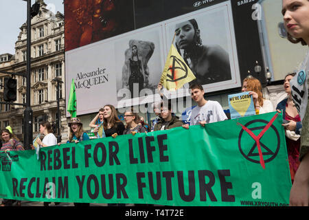 Beneath advertising, young campaigners block Piccadilly Circus  on day 4 of protests by climate change environmental activists with pressure group Extinction Rebellion, on18th April 2019, in London, England. - Stock Image