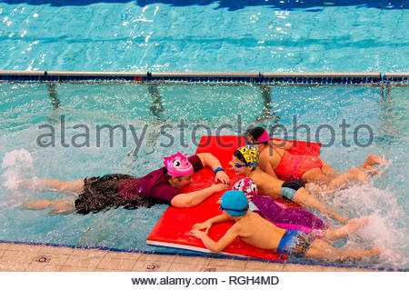 Poznan, Poland - January 26, 2019: Instructor and three children holding on a mat during swim lessons in a indoor pool of the Termy Maltanskie. - Stock Image