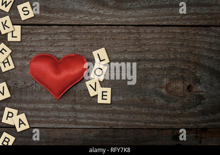 A red fabric heart on a wooden table with plastic letters that forms the word love - Stock Image