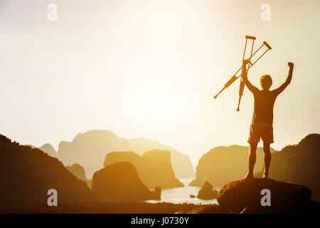 Man with crutches stands in winner pose with rised hands on mountains and islands background. Space for text - Stock Image