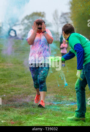Adult female walker with hands over her face being covered in paint on Macmillan cancer charity 5K colour fun run. - Stock Image