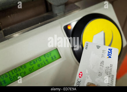 Someone using a Contactless Visa card being for travel payment on a London underground station - Stock Image