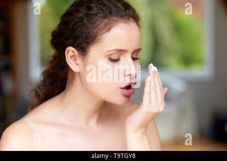 Woman smelling her own breathe - Stock Image