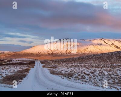 A snow covered road leading towards a sunlit mountain in Iceland - Stock Image