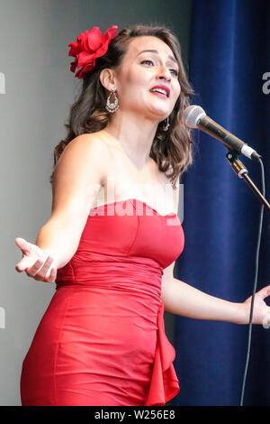 Miami Beach Florida North Beach Band Shell free community event stage woman singer singing microphone hand gesture performing expressive Hispanic clas - Stock Image