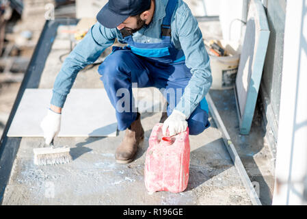 Workman in uniform priming concrete with brush for tiles lying on the balcony - Stock Image
