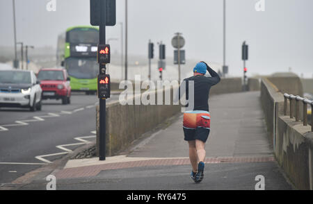 Brighton, UK. 12th Mar, 2019. A runner hangs on to his hat on Brighton seafront this morning as Storm Gareth starts to batter Britain and Ireland with winds expected to reach over 70mph in some areas Credit: Simon Dack/Alamy Live News - Stock Image